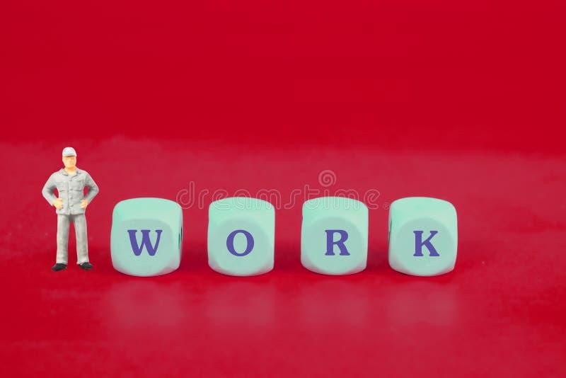 Ο μικροσκοπικός εργαζόμενος με τη λέξη εργασίας χωρίζει σε τετράγωνα επάνω, στοκ εικόνες