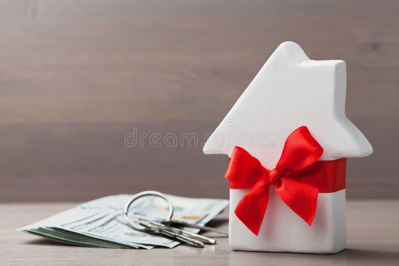 Ο μικρός Λευκός Οίκος διακόσμησε την κόκκινη κορδέλλα τόξων με τη δέσμη των κλειδιών και των χρημάτων μετρητών στον ξύλινο πίνακα στοκ φωτογραφίες με δικαίωμα ελεύθερης χρήσης