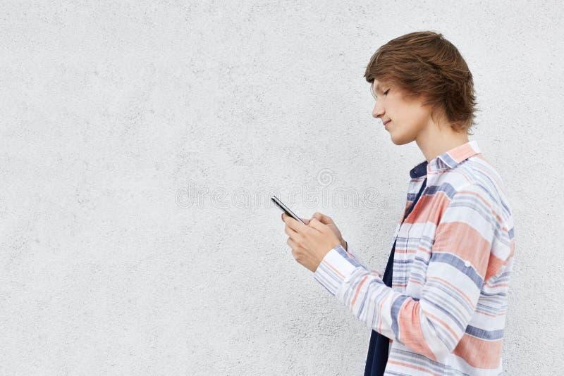 Ο μοντέρνος έφηβος που στέκεται λοξά το τηλέφωνο κυττάρων απομονώνει στοκ εικόνα