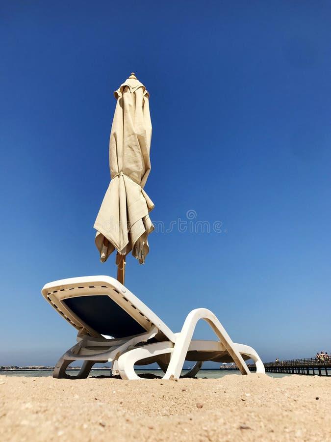 Ο μοντέρνος αργόσχολος στην κίτρινη άμμο στον ήλιο στην παραλία το καλοκαίρι κάτω από το ανοιχτό ουρανό στοκ φωτογραφία με δικαίωμα ελεύθερης χρήσης
