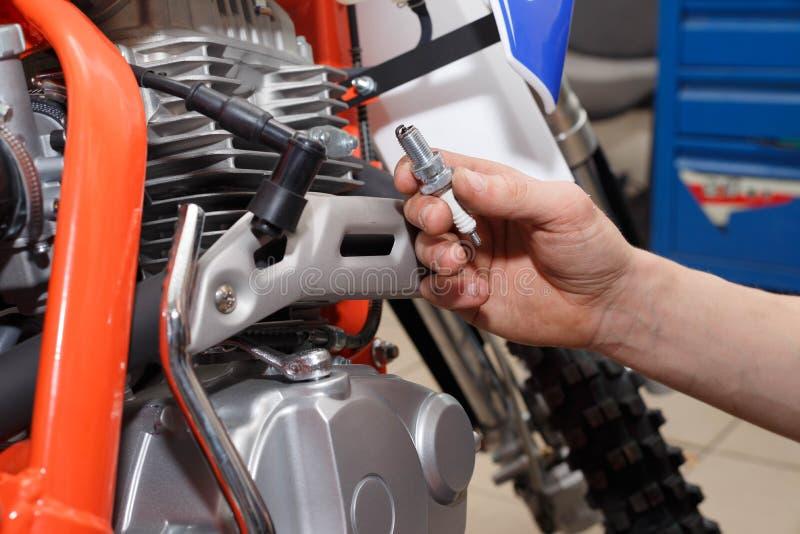 Ο μοτοσυκλετιστής αντικαθιστά, ελέγχει το βούλωμα πυράκτωσης σε μια μοτοσικλέτα στοκ εικόνες