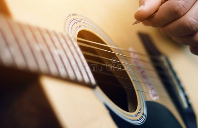 Ο μουσικός γρατζουνά μια μελωδία σε μια ακουστική κιθάρα, που κρατά έναν μεσολαβητή στοκ εικόνα με δικαίωμα ελεύθερης χρήσης