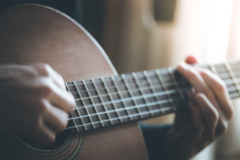 Ο μουσικός παίζει μια κλασσική κιθάρα, fretboard και τα δάχτυλα στοκ φωτογραφία