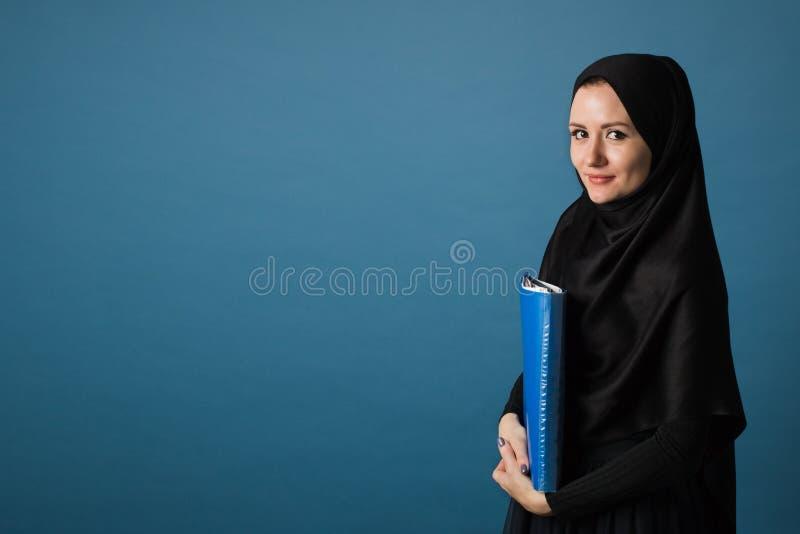 Ο μουσουλμανικός γραμματέας κοριτσιών ή ο διευθυντής γραφείων στο hijab στέκεται με έναν φάκελλο των εγγράφων στα χέρια της σε έν στοκ φωτογραφία με δικαίωμα ελεύθερης χρήσης