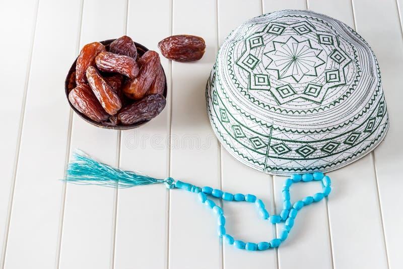 Ο μουσουλμανικός ισλαμικός σκούφος έννοιας taqiyah, μπλε rosary και οι ημερομηνίες medjul στην καρύδα shel κυλούν στοκ φωτογραφία με δικαίωμα ελεύθερης χρήσης