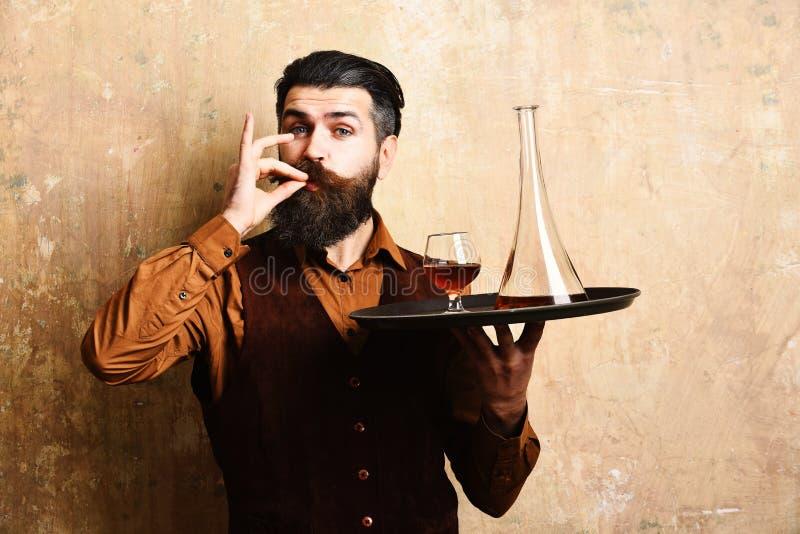 Ο μπάρμαν με το ικανοποιημένο πρόσωπο εξυπηρετεί σκωτσέζικο Σερβιτόρος με το γυαλί, μπουκάλι στοκ εικόνα