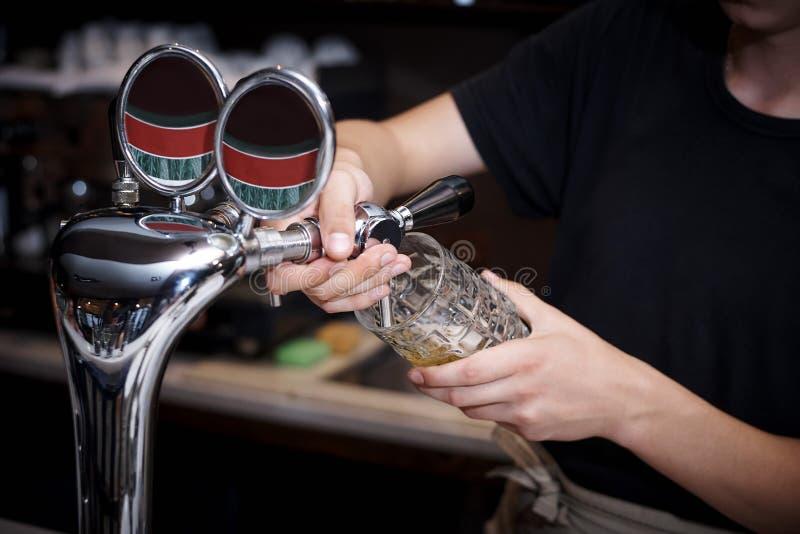 Ο μπάρμαν χύνει την μπύρα στοκ φωτογραφία