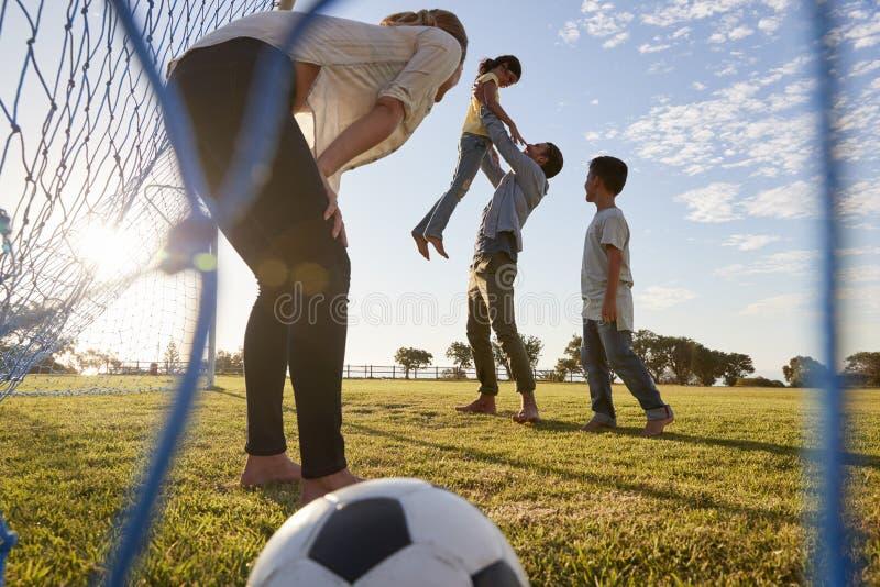 Ο μπαμπάς ανυψώνει την κόρη του κατά τη διάρκεια ενός οικογενειακού ποδοσφαιρικού παιχνιδιού στοκ φωτογραφία