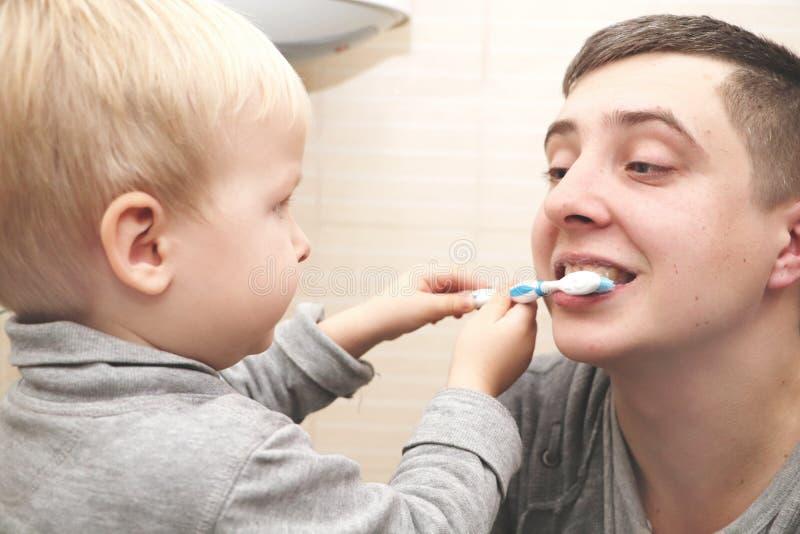 Ο μπαμπάς και ο γιος βουρτσίζουν τα δόντια τους στο λουτρό Δόντια βουρτσίσματος πατέρων στο παιδί στοκ φωτογραφία