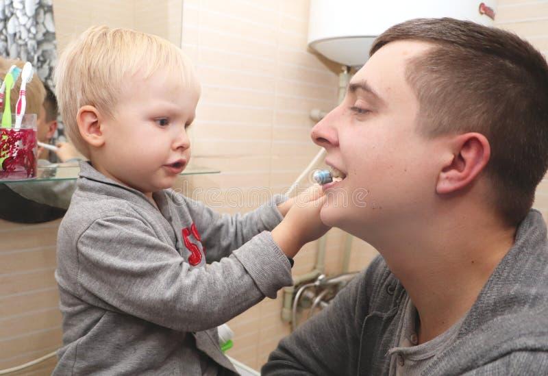 Ο μπαμπάς και ο γιος βουρτσίζουν τα δόντια τους στο λουτρό Δόντια βουρτσίσματος πατέρων στο παιδί στοκ εικόνες