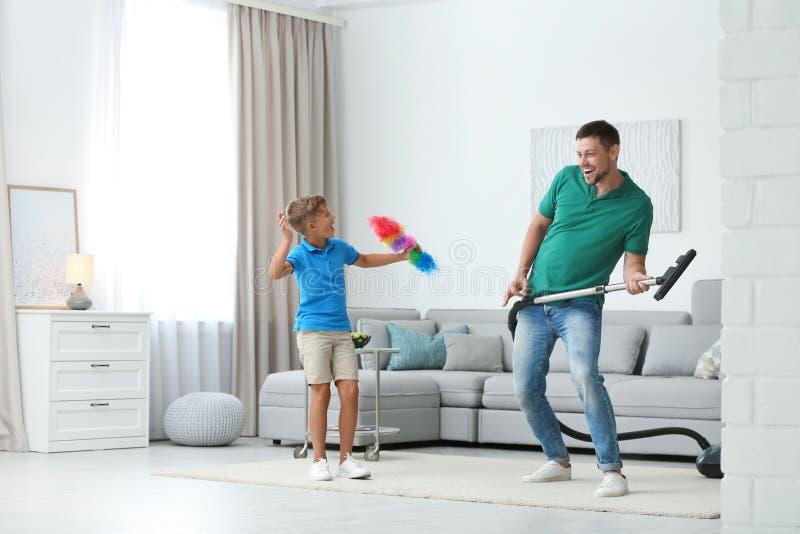 Ο μπαμπάς και ο γιος διασκεδάζουν ενώ καθαρίζουν το σαλόνι στοκ εικόνα