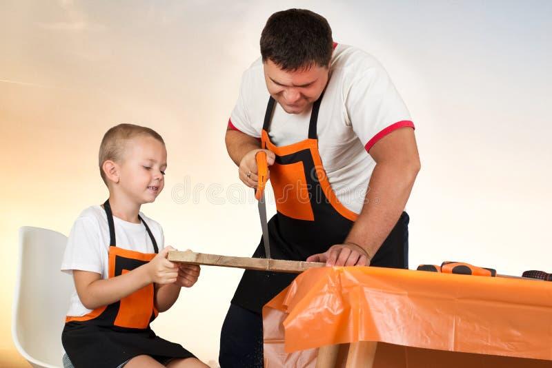 Ο μπαμπάς και ο γιος του εργάζονται στο εργαστήριο Πριονίζουν τις ξύλινες σανίδες στοκ εικόνα