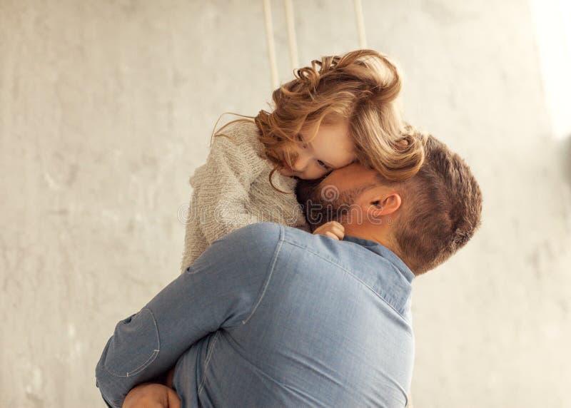 Ο μπαμπάς και η κόρη αγκαλιάζουν στο σπίτι στοκ εικόνα με δικαίωμα ελεύθερης χρήσης