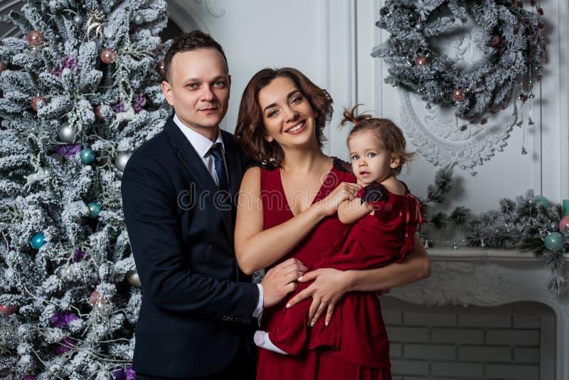 Ο μπαμπάς και η κόρη Mom που ντύνονται σε ένα μοντέρνο κοστούμι και ένα κομψό κόκκινο βράδυ ντύνουν σε ένα κοσμικό κόμμα προς τιμ στοκ εικόνες με δικαίωμα ελεύθερης χρήσης