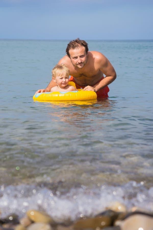 Ο μπαμπάς και ο γιος λούζουν στη θάλασσα στοκ εικόνα