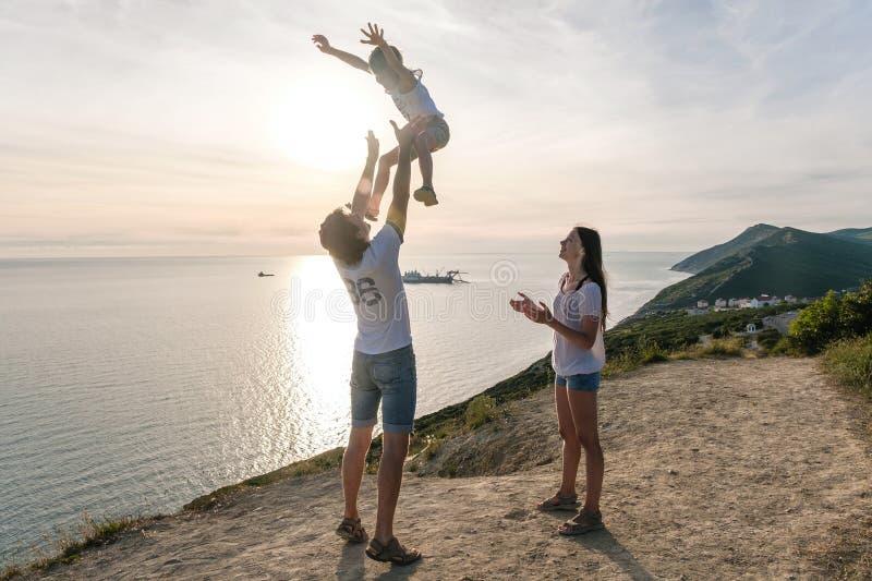 Ο μπαμπάς ρίχνει το γιο του στον αέρα, και mom εξετάζει τους στο βουνό με seascape Οικογενειακό ταξίδι στοκ φωτογραφία με δικαίωμα ελεύθερης χρήσης