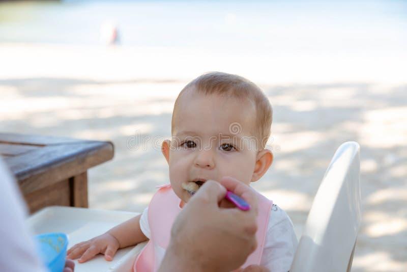 Κοριτσάκι που τρώει το κουάκερ Ο μπαμπάς ταΐζει λίγη κόρη με ένα κουτάλι Ενάντια στο σκηνικό μιας τροπικής παραλίας στοκ φωτογραφίες με δικαίωμα ελεύθερης χρήσης