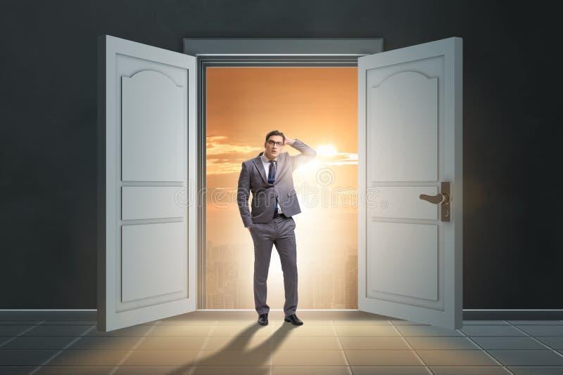 Ο μπερδεμένος επιχειρηματίας μπροστά από τη μεγάλη πόρτα στοκ φωτογραφίες