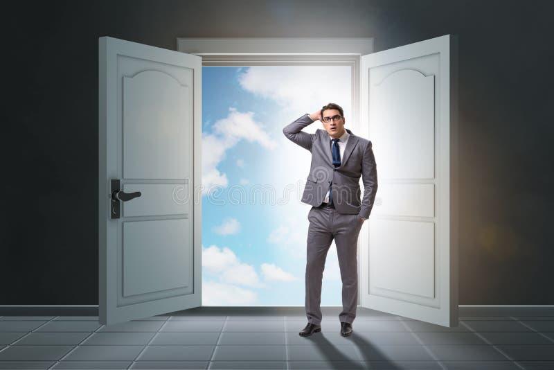 Ο μπερδεμένος επιχειρηματίας μπροστά από τη μεγάλη πόρτα στοκ εικόνες
