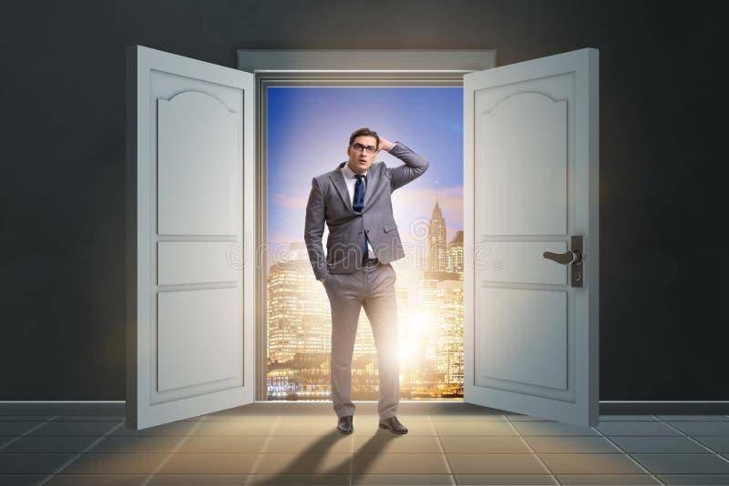 Ο μπερδεμένος επιχειρηματίας μπροστά από τη μεγάλη πόρτα στοκ εικόνα με δικαίωμα ελεύθερης χρήσης