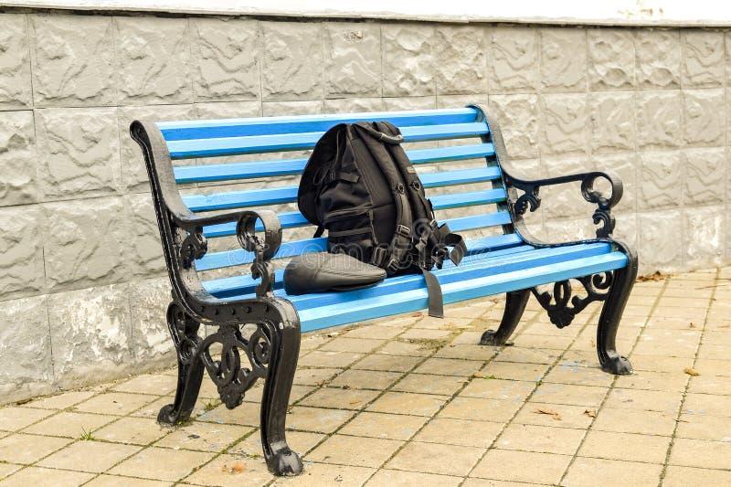 Ο μπλε πάγκος στο πάρκο στο κεραμωμένο πεζοδρόμιο κανένα σώμα στοκ φωτογραφία με δικαίωμα ελεύθερης χρήσης
