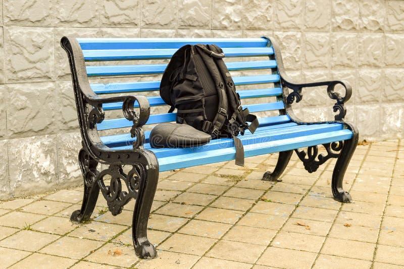 Ο μπλε πάγκος στο πάρκο στο κεραμωμένο πεζοδρόμιο κανένα σώμα στοκ εικόνα