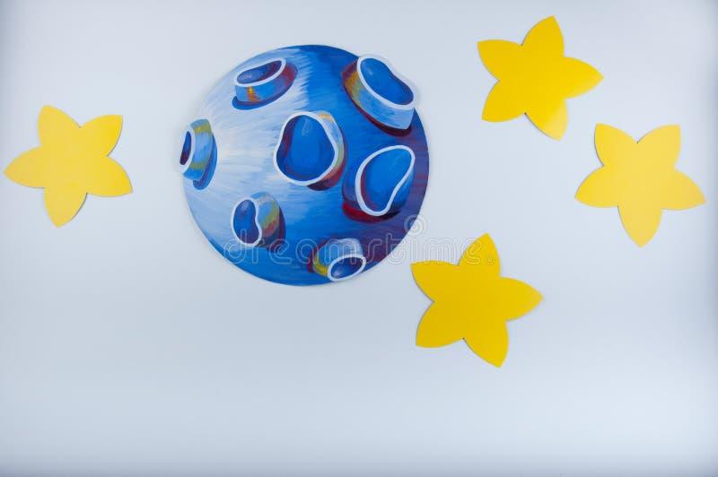 Ο μπλε συρμένος πλανήτης και τα κίτρινα αστέρια γύρω από βάζουν στο άσπρο υπόβαθρο στοκ εικόνες