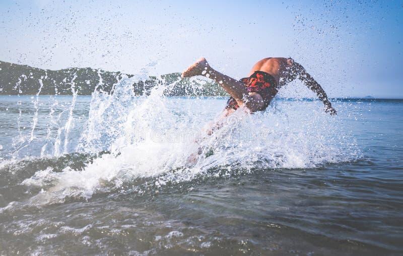 Ο μυϊκός νεαρός άνδρας βουτά από την ακτή μέσα στη θάλασσα στοκ φωτογραφία με δικαίωμα ελεύθερης χρήσης