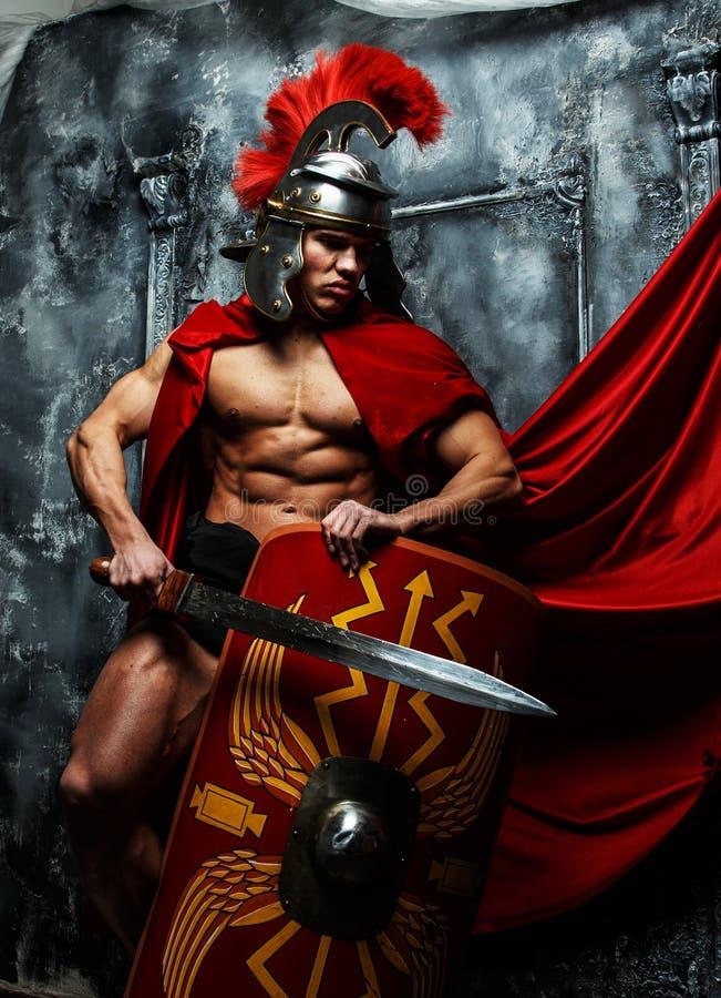 Ο μυϊκός πολεμιστής κρατά την ασπίδα και το ξίφος στοκ εικόνα με δικαίωμα ελεύθερης χρήσης