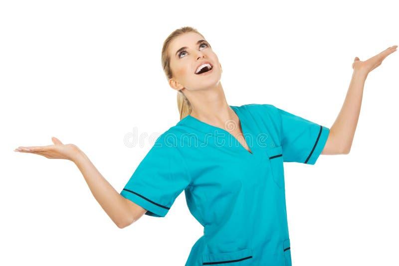 Ο νέα γιατρός ή η νοσοκόμα γυναικών χαμόγελου πιάνει κάτι από τον αέρα στοκ εικόνες