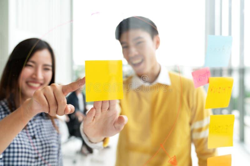 Ο νέοι επιτυχείς δημιουργικοί άνδρας και η γυναίκα χαμογελούν και καταιγισμός ιδεών στο πρόγραμμα στο γραφείο στοκ φωτογραφία με δικαίωμα ελεύθερης χρήσης