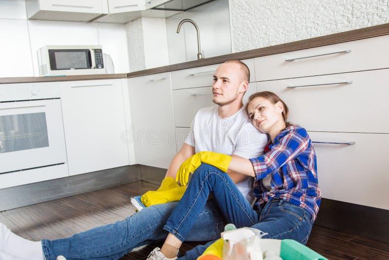 Ο νέοι σύζυγος και η σύζυγος ζευγών κάνουν τον καθαρισμό σπιτιών Ο τύπος και το κορίτσι πλένουν την κουζίνα με μια σφουγγαρίστρα  στοκ εικόνες