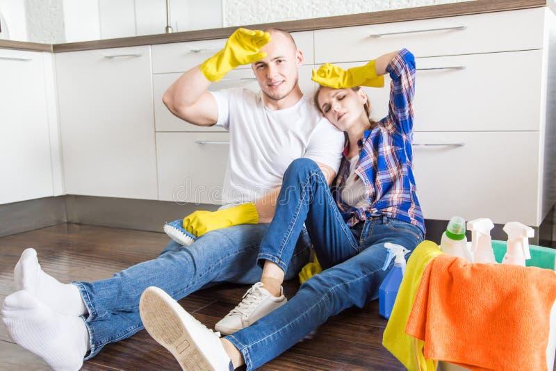 Ο νέοι σύζυγος και η σύζυγος ζευγών κάνουν τον καθαρισμό σπιτιών Ο τύπος και το κορίτσι πλένουν την κουζίνα με μια σφουγγαρίστρα  στοκ φωτογραφίες