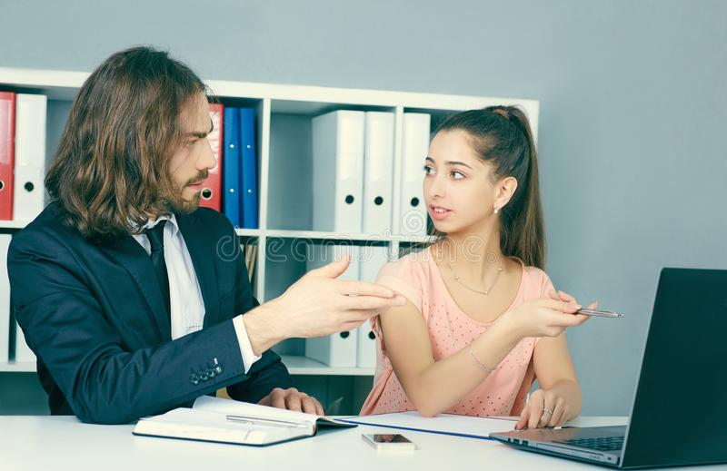 Ο νέος άνδρας υπάλληλος της ασφαλιστικής αντιπροσωπείας εισάγει σε μια σύμβαση με ένα κορίτσι Επιχείρηση, γραφείο, νόμος και νομι στοκ φωτογραφίες με δικαίωμα ελεύθερης χρήσης