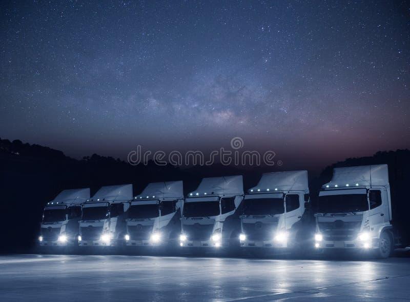 Ο νέος άσπρος στόλος φορτηγών μεταφορών σταθμεύει τη νύχτα με την αστρονομία milkyway στοκ φωτογραφίες