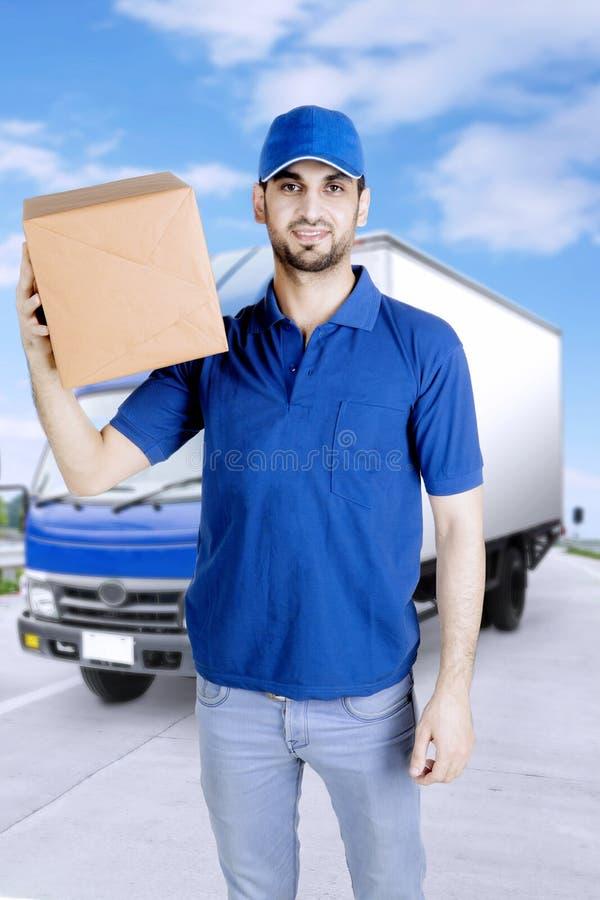 Ο νέος αγγελιαφόρος κρατά το κιβώτιο κοντά στο φορτηγό του στοκ φωτογραφία με δικαίωμα ελεύθερης χρήσης