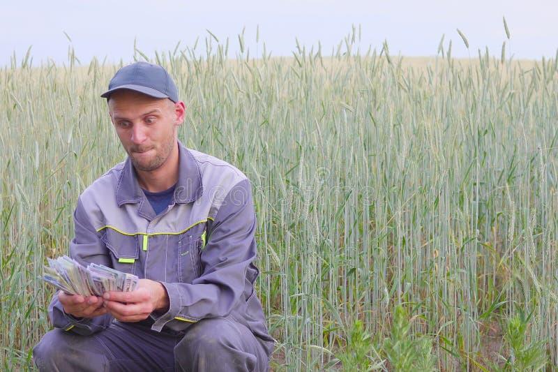 Ο νέος αγρότης έχει πολλά χρήματα Η έννοια της επιτυχίας της επιχείρησης στη γεωργία στοκ εικόνες