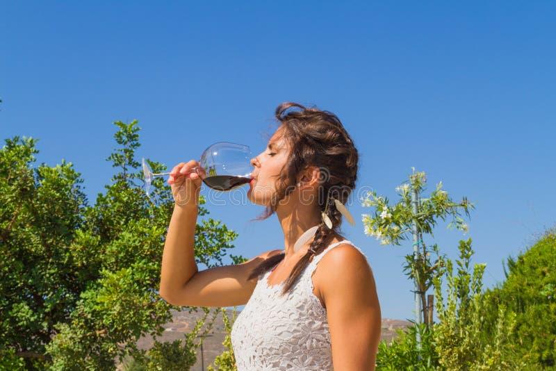 Ο νέος αγρότης γυναικών δοκιμάζει ένα ποτήρι του κόκκινου κρασιού στοκ εικόνες