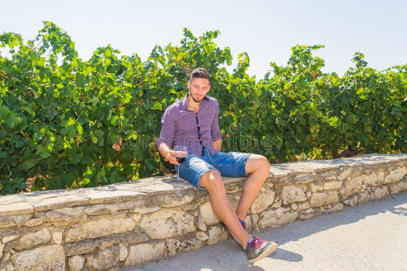 Ο νέος αγρότης δοκιμάζει ένα ποτήρι του κόκκινου κρασιού στοκ φωτογραφία με δικαίωμα ελεύθερης χρήσης