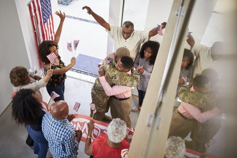 Ο νέος αρσενικός στρατιώτης αφροαμερικάνων χαιρέτισε το σπίτι από την οικογένεια τριών γενεάς, ανυψωμένη άποψη στοκ φωτογραφίες