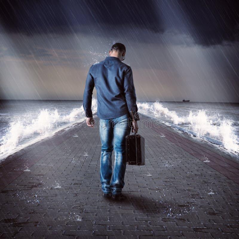 Ο νέος αρσενικός ταξιδιώτης είναι στην αποβάθρα κατά τη διάρκεια της θύελλας στοκ φωτογραφίες με δικαίωμα ελεύθερης χρήσης