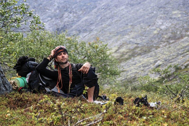 Ο νέος αρσενικός τουρίστας κάθισε για να στηριχτεί σε ένα πεζοπορώ βουνών στοκ εικόνες