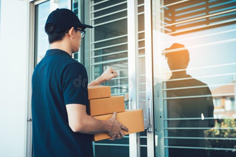 Ο νέος ασιατικός αγγελιαφόρος χρησιμοποιεί το χέρι του κτύπου στην πόρτα για να παραδώσει τα αγαθά στοκ φωτογραφίες με δικαίωμα ελεύθερης χρήσης