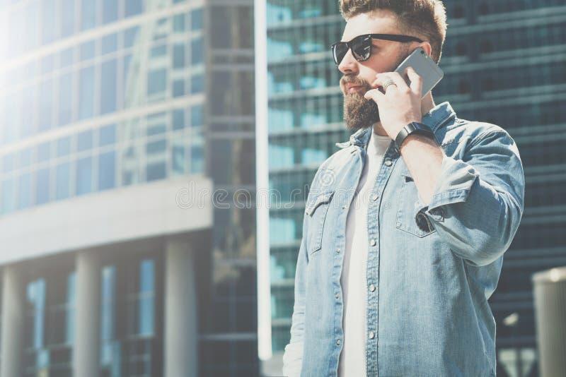 Ο νέος γενειοφόρος επιχειρηματίας στα γυαλιά ηλίου και το πουκάμισο τζιν στέκεται στην οδό πόλεων και μιλά στο τηλέφωνο κυττάρων  στοκ φωτογραφία με δικαίωμα ελεύθερης χρήσης