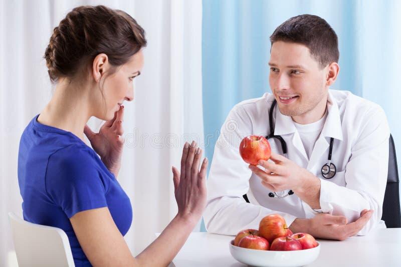 Ο νέος γιατρός προτείνει το μήλο συναδέλφων στοκ εικόνες με δικαίωμα ελεύθερης χρήσης