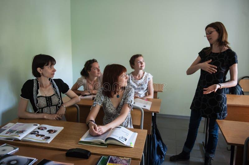 Ο νέος δάσκαλος ξένης γλώσσας γυναικών σε μια μικρή τάξη δίνει στους σπουδαστές ένα μάθημα eps αρχείο, κάθε στοιχείο ομαδοποιείτα στοκ εικόνες