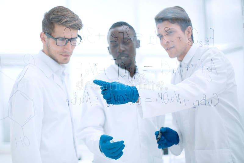 Ο νέος επιστήμονας παρουσιάζει ένα δάχτυλο στον πίνακα γυαλιού στοκ εικόνα