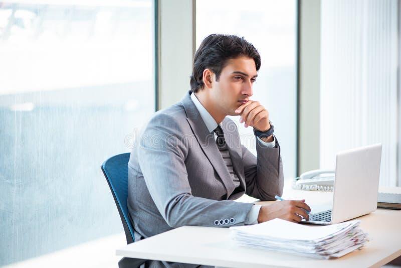 Ο νέος επιτυχής επιχειρηματίας που εργάζεται στο γραφείο στοκ φωτογραφία