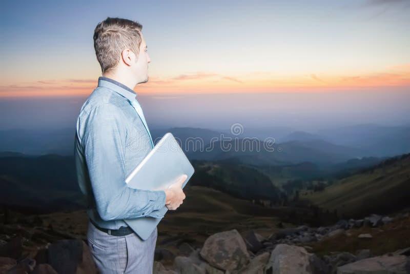 Ο νέος επιχειρηματίας κάθεται πάνω από το βουνό στοκ εικόνα με δικαίωμα ελεύθερης χρήσης