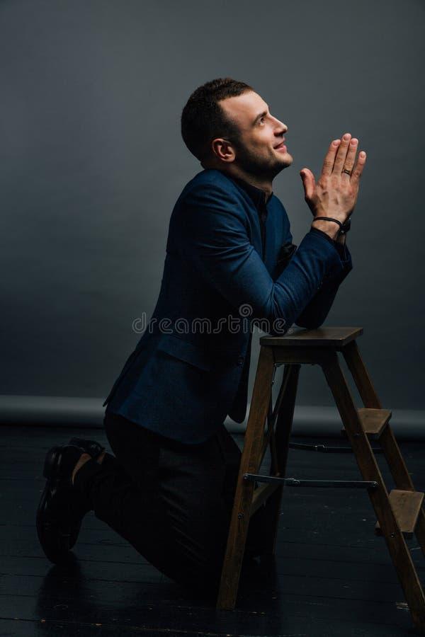 Ο νέος επιχειρηματίας προσεύχεται στα γόνατα εκτός από τις ξύλινες σκάλες Φοίνικες στο πρόσωπο, κακόβουλα στοκ φωτογραφίες με δικαίωμα ελεύθερης χρήσης